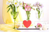 Freesias in glasses on table — Stock Photo