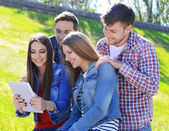Students sitting in park — Stock Photo