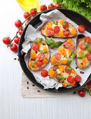 Tasty bruschetta with tomatoes in pan — Stock Photo