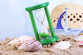 Hourglass in sand on blue sky background — Stock Photo