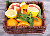 Fresh citrus fruits with green leaves in wicker basket — Stok fotoğraf