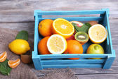 Fresh exotic fruits with green leaves in wooden box — Stockfoto