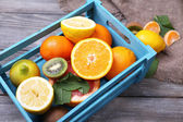 Fresh exotic fruits with green leaves in wooden box — Stock Photo
