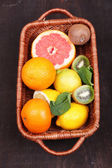 Fresh exotic fruits with green leaves in wicker basket — Stock Photo