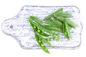 Fresh green peas on wooden board — Stok fotoğraf