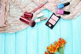 Eyeshadow, brushes, lipstick and flowers — Stock Photo