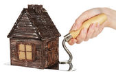 Hand holding wooden toy house on trowel — Stock Photo