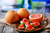 Ripe grapefruits on tray, on wooden table, on bright background — Стоковое фото