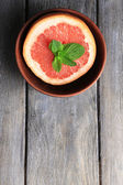 Part of ripe grapefruit in bowl, on wooden background — Stock Photo