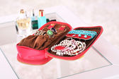 Handbag with accessorises and perfumes in bottles on table — Stock Photo