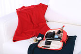 Cosmetic bag, fashion clothes, bottle of perfumes on sofa — Stock Photo