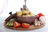 Young boiled potatoes in pan with vegetables on table in kitchen — Stock Photo