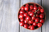 Sweet cherries in color bowl on wooden background — Stok fotoğraf