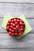 Sweet cherries in color bowl on wooden background — Zdjęcie stockowe