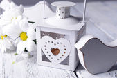 White lantern with flowers on wooden table — Stock Photo