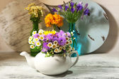 Kitchen decoration with teapot and wild flowers — Stock Photo