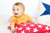 Cute baby boy lying with pillow on floor in room — Stock Photo