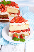 Delicious biscuit cake with strawberries on table — Stock Photo
