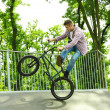 Young boy jumping with his BMX Bike at skate park — Stock Photo #48741459