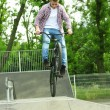 Young boy jumping with his BMX Bike at skate park — Stock Photo #48741465