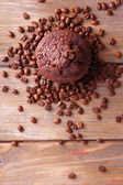 Chocolate muffin and coffee grains on wooden background — Stock Photo