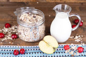 Homemade granola in glass jar, fresh cherries and jug with milk on color wooden background — Stockfoto