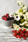 Flowers and berries on wooden table — Foto Stock
