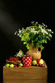 Still life with flowers and fruits on dark background — Stock Photo