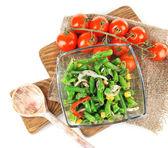Салат с зеленой фасолью, ветчиной и кукурузы в стеклянную емкость, на деревянной доске, изолированные на белом — Стоковое фото