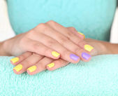 Female hand with stylish colorful nails, on color towel, close-up — Stock Photo