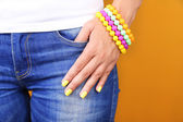 Female hand with stylish colorful nails, close-up, on color background — Stock Photo