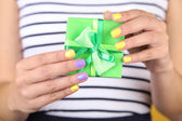 Woman with stylish colorful nails holding gift box, close-up, on color background — Photo
