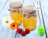 Jar full of delicious fresh honey and wild flowers on wooden table — Foto Stock