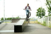 Young boy jumping with his BMX Bike at skate park — 图库照片