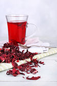 Hibiscus tea and flower on color napkin on wooden table, on light background — Stock Photo