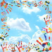 Frame of color hands print on sky background — Stock Photo