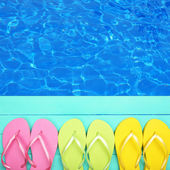 Colored flip flops on wooden platform beside sea — Stock Photo