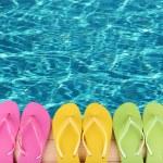Colored flip flops on wooden platform beside sea — Stock Photo #48897515