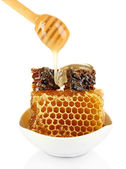 Honey dripping on honeycombs isolated on white — Photo