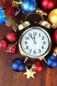 Alarm clock with Christmas decorations on wooden background — Stock Photo
