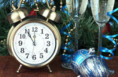 Alarm clock with Christmas tree and stemware on table close up — Zdjęcie stockowe