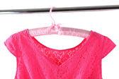 Beautiful pink dress hanging on hangers — Stock Photo