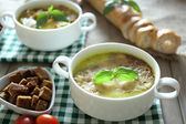 Tasty soup in saucepans — Stock Photo