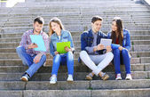 Students sitting on stairs in park — Stock Photo