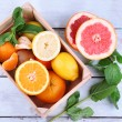 Fresh citrus fruits with green leaves in wooden box — Stock Photo #48900289