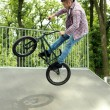 Boy jumping with his BMX Bike — Stock Photo #48905443
