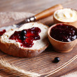 Fresh toast with homemade butter and blackcurrant jam on wooden background — Stock Photo #48905819