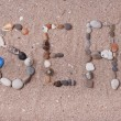 Word sea made from sea shells and stones on sand — Stock Photo #48906361