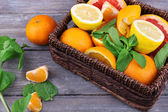 Fresh citrus fruits with green leaves in wicker basket on wooden background — 图库照片