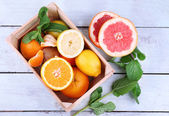 Fresh citrus fruits with green leaves in wooden box — Photo